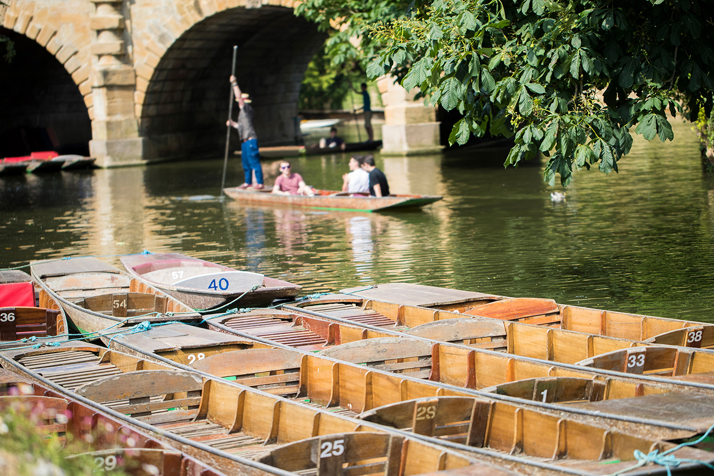 People punting on the river in Oxford, with boats in the foreground and Magdalen Bridge in the distance