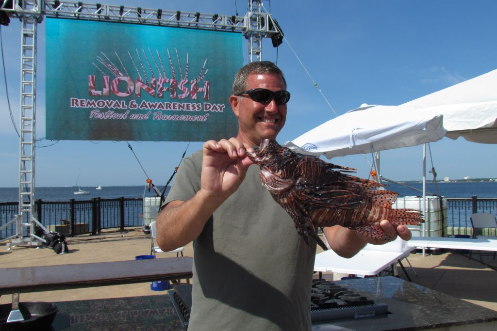 A man holding a large Lionfish caught at the Pensacola Lionfish Classic