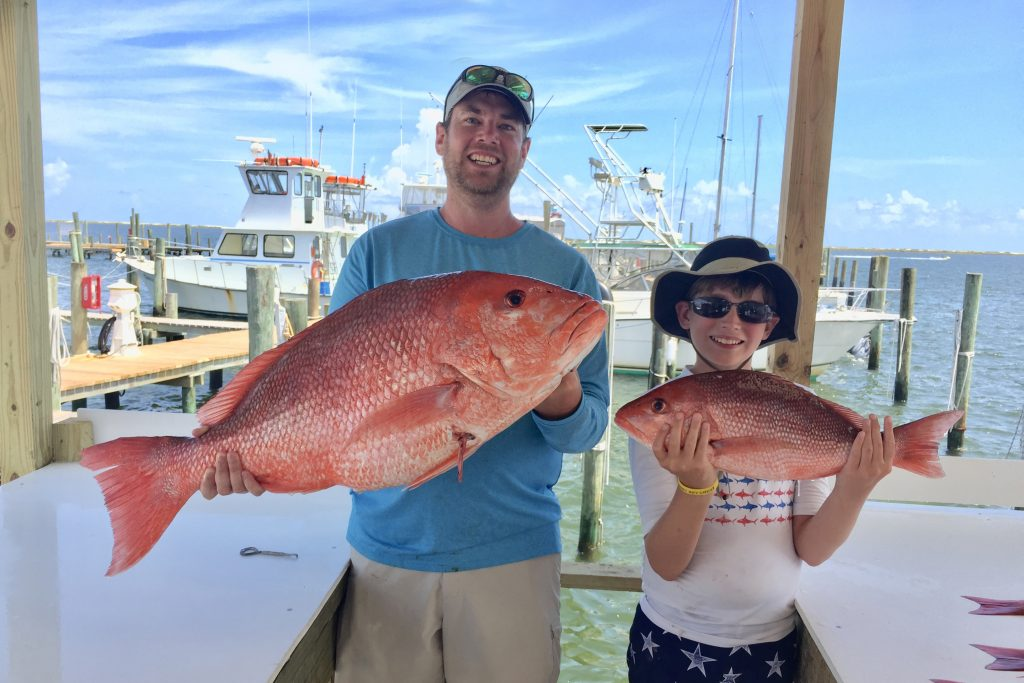 A man and a boy holding red and vermilion snapper caught on a fishing trip out of Pensacola, FL