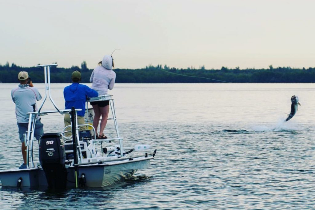 A woman fighting a Tarpon on a fishing charter in Pensacola, with two other anglers on the boat watching