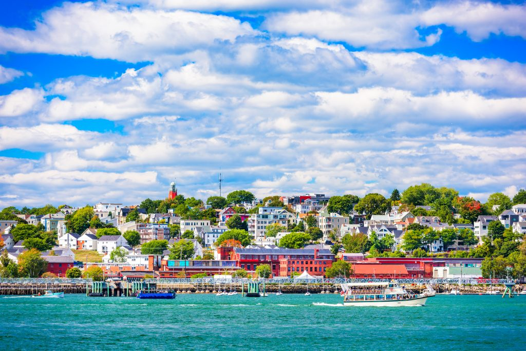 A view of Portland, Maine, from the water, with colorful buildings and boats docking at the waterfront
