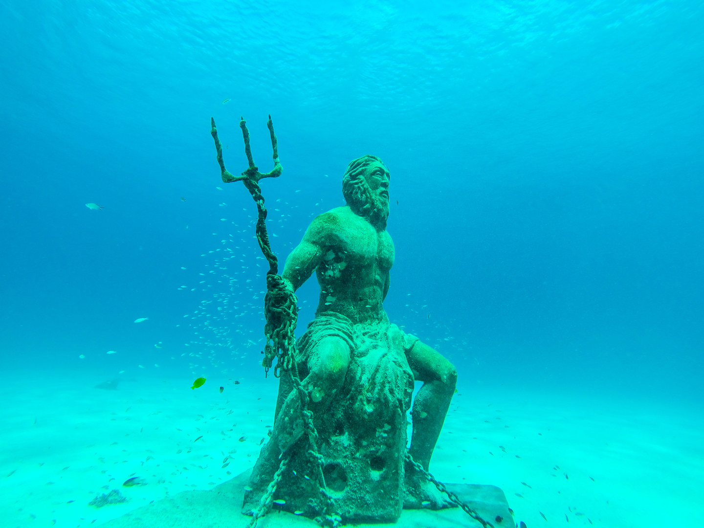 a submerged statue of Poseidon holding his trident