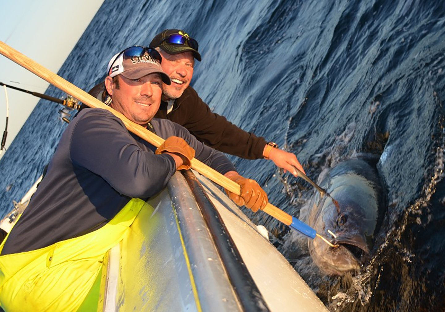 Two anglers leaning over the side of a boat next to a giant Bluefin Tuna. One is holding a gaff hook attached to the Tuna's mouth.