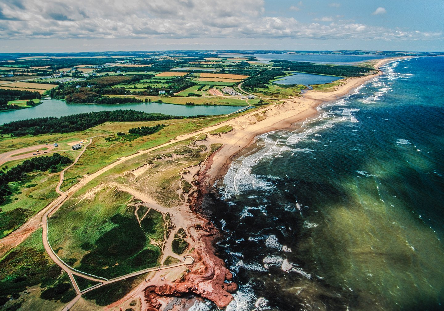 An aerial view of Prince Edward Island in Canada, with green fields on the left, yellow beach in the middle, and dark green water on the right.