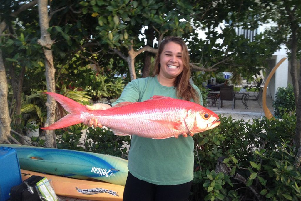 A smiling woman holding a Caribbean Queen Snapper