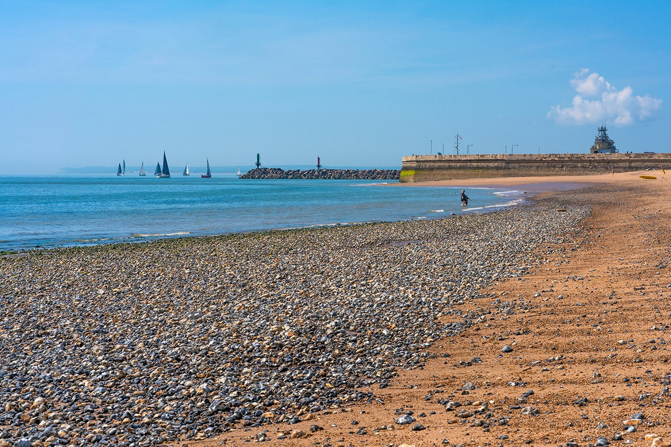 Ramsgate Beach at low tide, with the harbour wall and sailboats in the distance