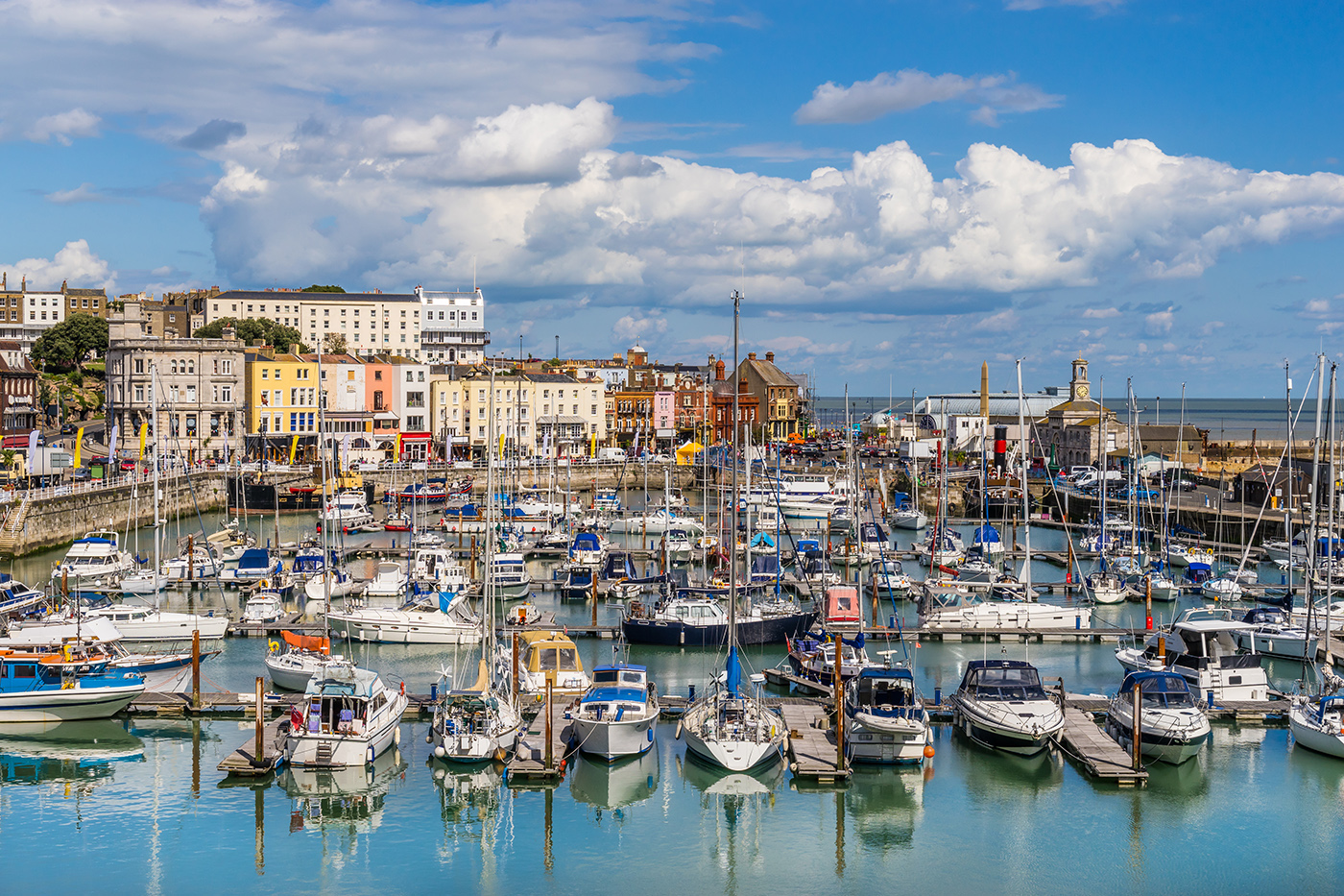 A sunny day at Ramsgate Harbour, with boats in the water and pretty buildings in the distance