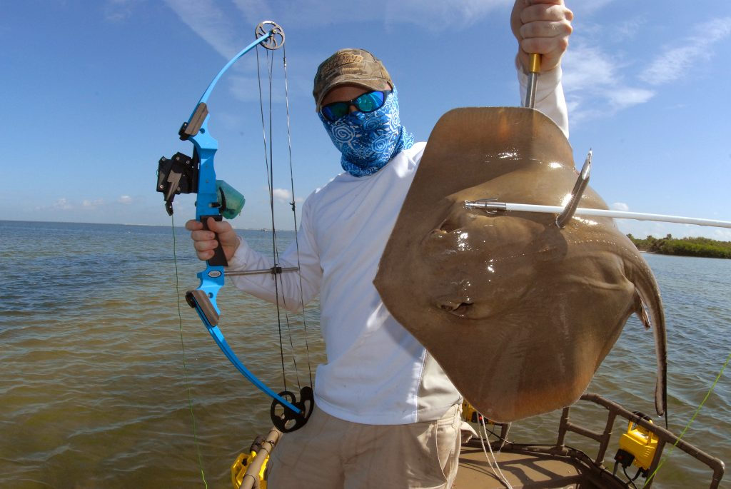 a bowfisher holding a Ray on a fishing boat. Rays are a commong bowfishing catch