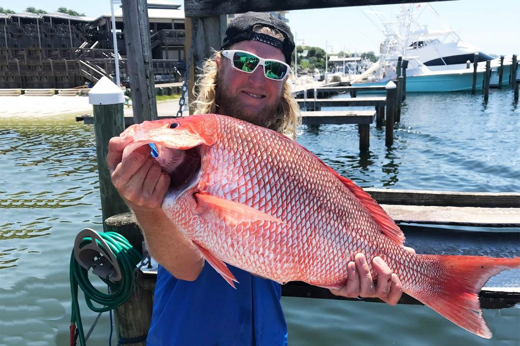 A smiling angler holds a large Red Snapper back ashore after a successful Destin fishing trip
