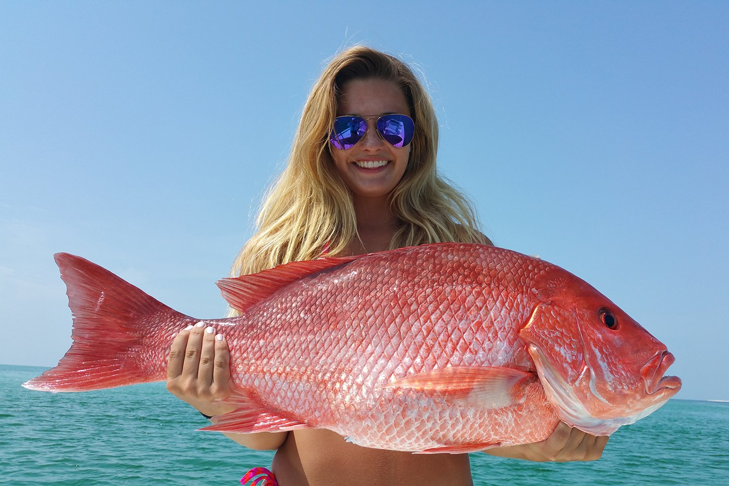Smiling blonde female angler holding a large Red Snapper