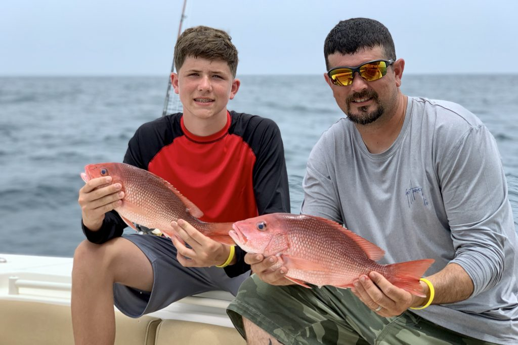 A man and a boy holding Red Snapper caught in the Gulf of Mexico