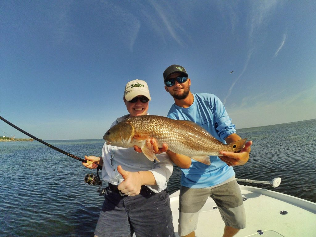An angler and a captain holding a beautiful Redfish
