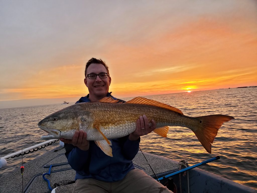 a smiling angler holding a redfish with the sun setting in the background