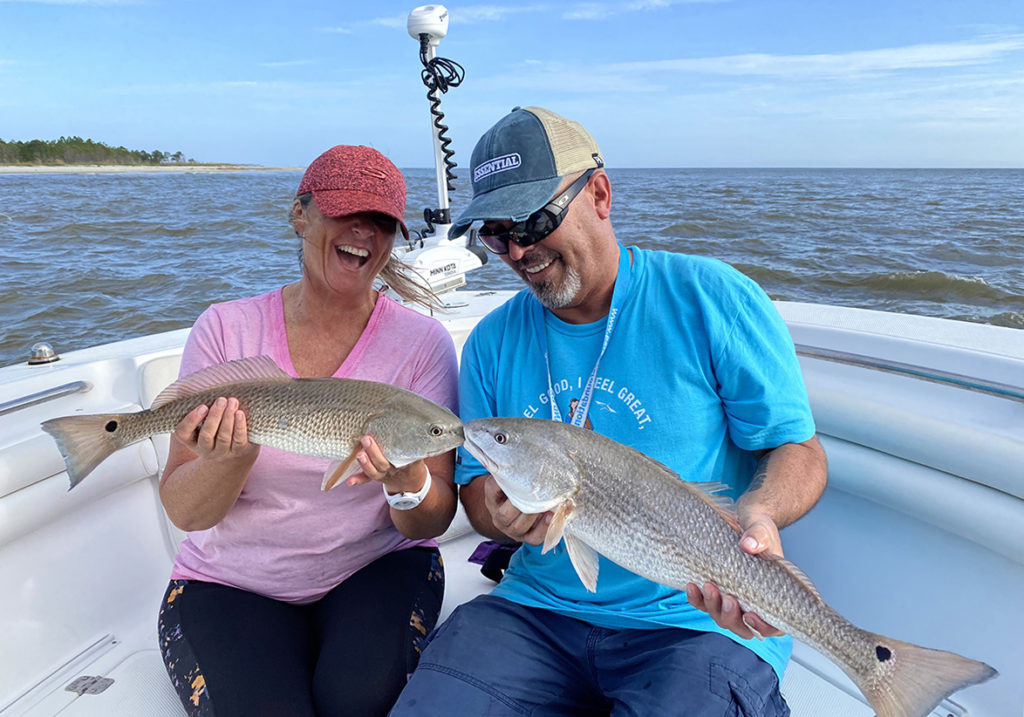 A woman and man sitting on a boat holding two Redfish with water and blue skies in the background