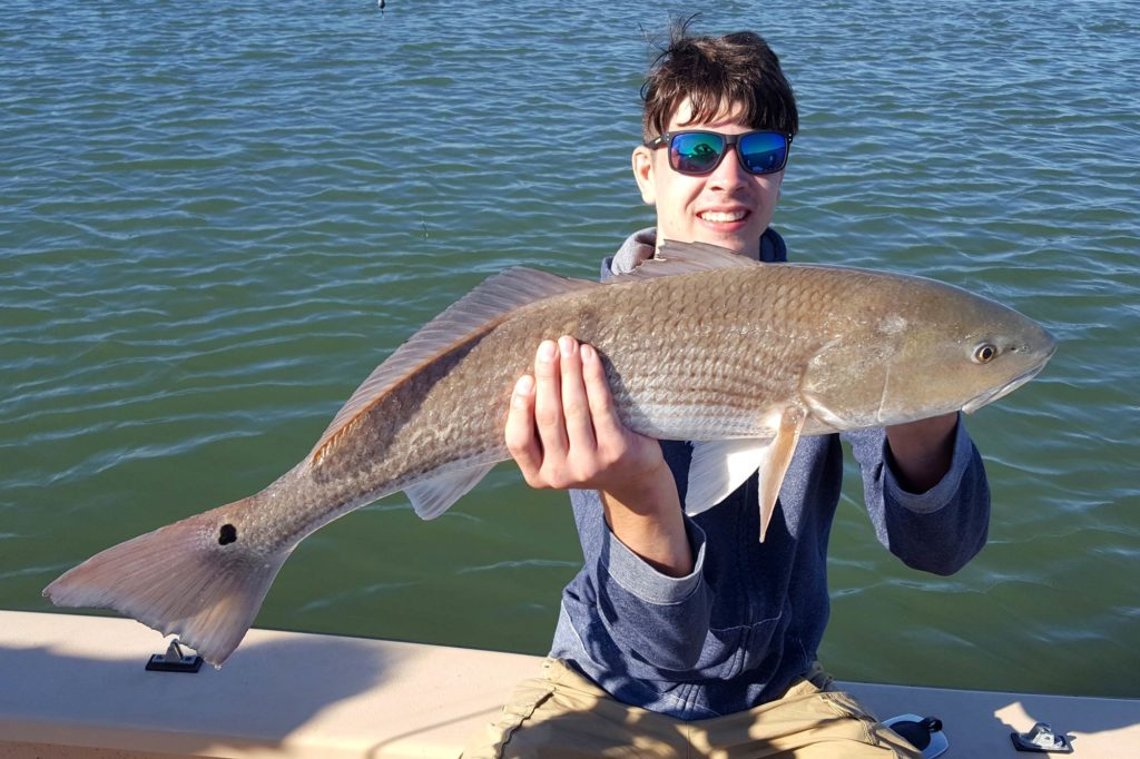 A teenage fisherman sitting on a boat with a big Redfish in his hands