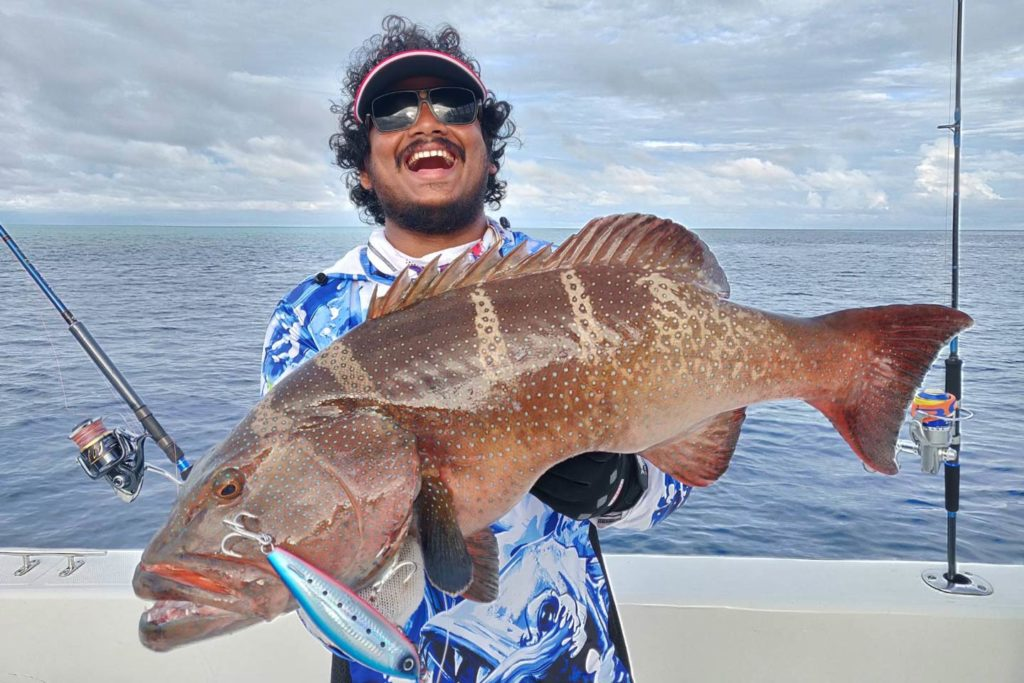 A happy angler showing off a fish caught over the reefs.