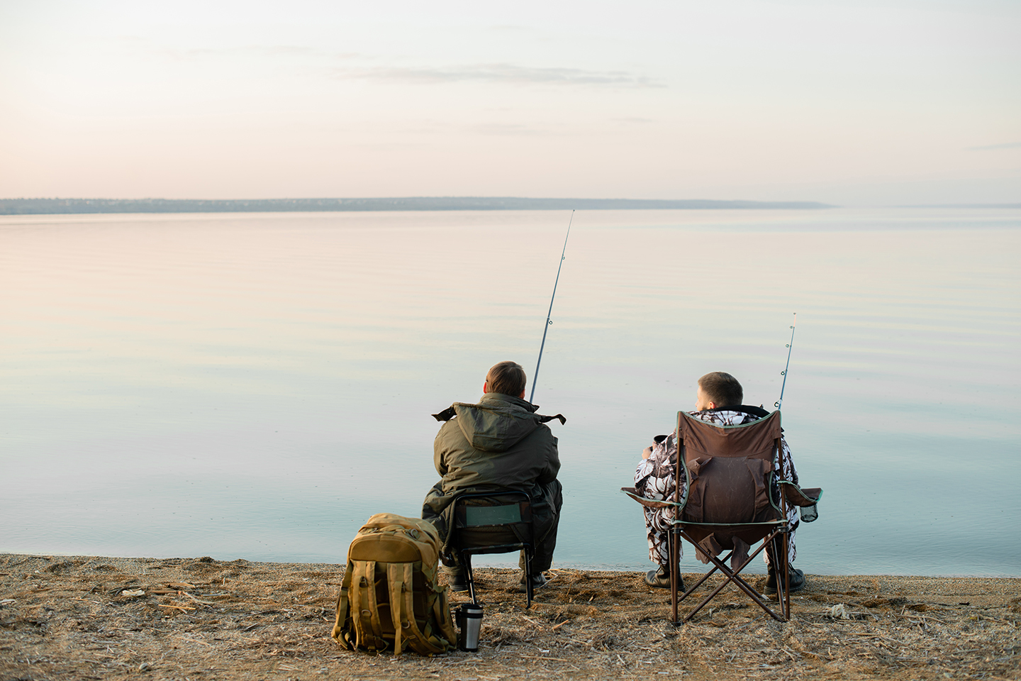 Two anglers sitting and fishing on the bank of a large lake