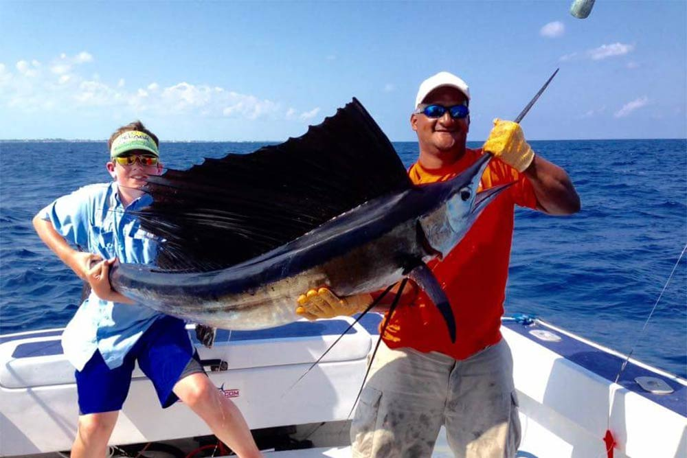 Two anglers hold a large Sailfish caught in Belize