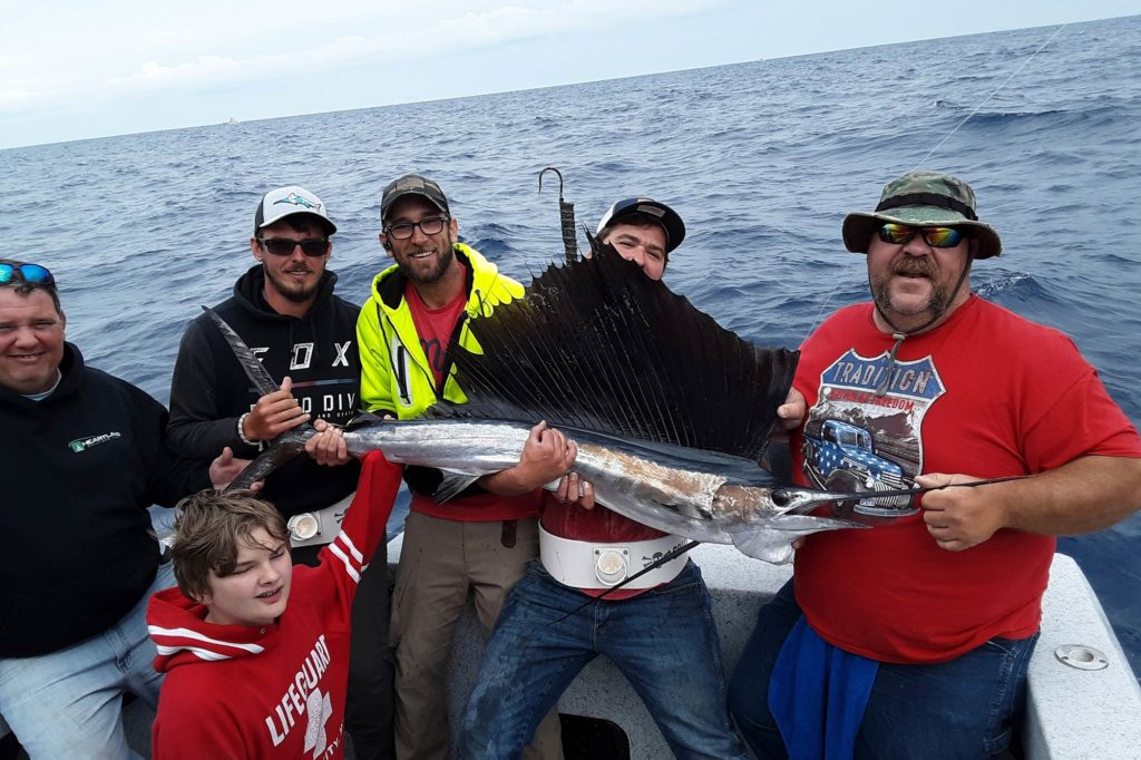 A group of fishermen sitting on a boat, holding a Sailfish