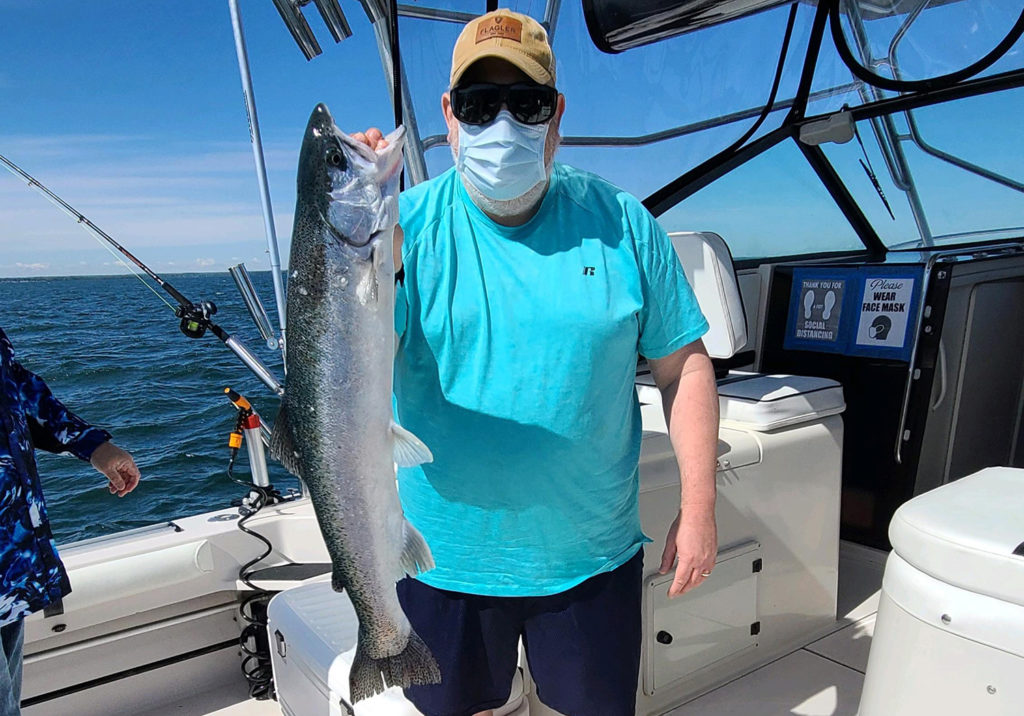 A fisherman with a mask standing on a boat, holding a Salmon