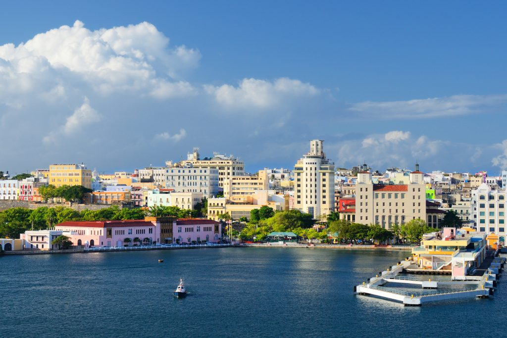 A pretty harbor in San Juan, Puerto Rico, with a boat heading out on a fishing trip.