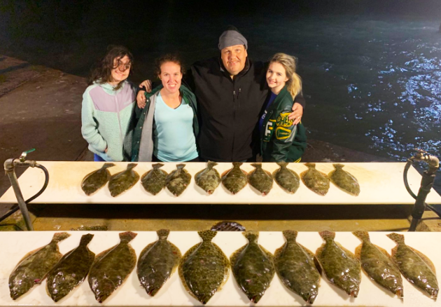 Family posing behind a table of Flounder