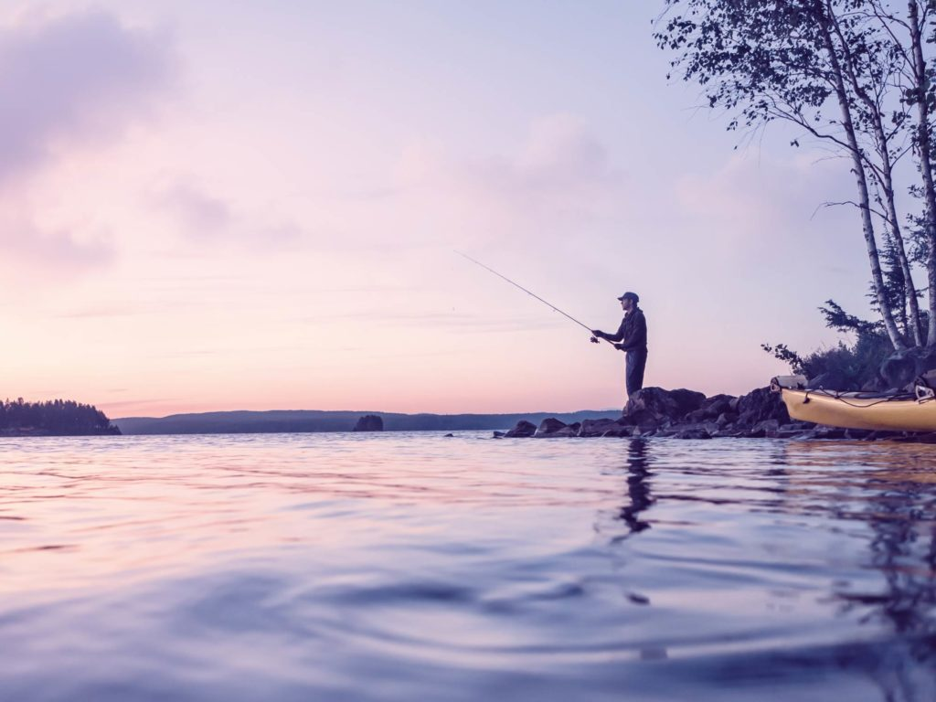 A lone angler standing at the edge of a rocky shore and fishing at dusk