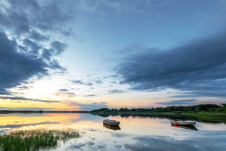 Fishing boats out on Western Jutland's Skanderborg Lakes at sunset.