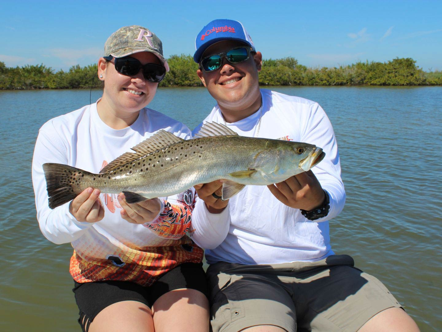 A smiling couple sit on board a vessel, holding a Speckled Trout with the Indian River in the background