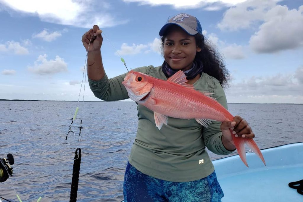 A female angler holds a Caribbean Queen Snapper caught on the reefs