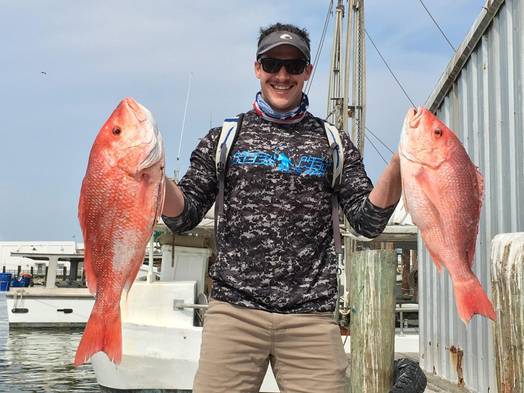 a smiling angler holding two Snapper fish