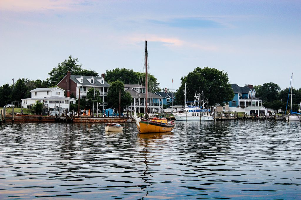 A sailboat moored near some houses in Solomons Island, Maryland.
