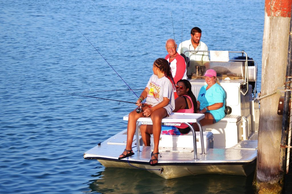 A family fishing on a small boat near a wooden jetty