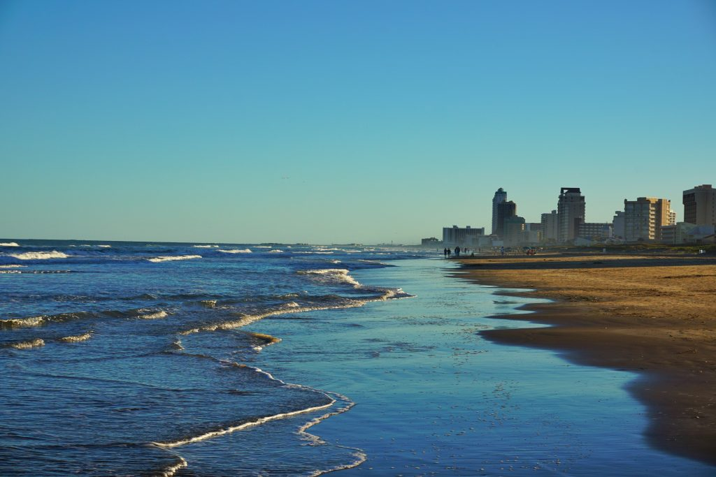 A view along the beach at South Padre Island, with hotels in the distance on the right