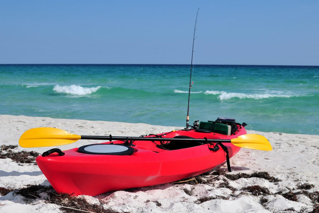 A red fishing kayak on a beach