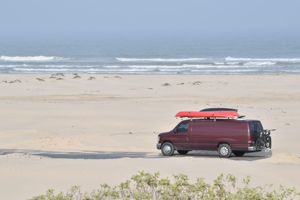 A van with kayaks on the roof driving along a beachside road on South Padre Island