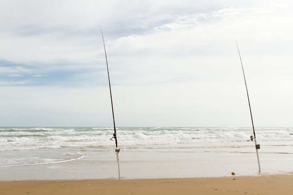 Two fishing rods set up in rod holders on a beach on South Padre Island