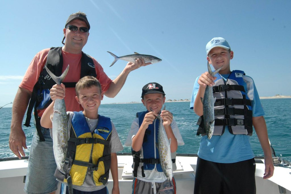 A man with three children holding Spanish Mackerel while standing on a boat
