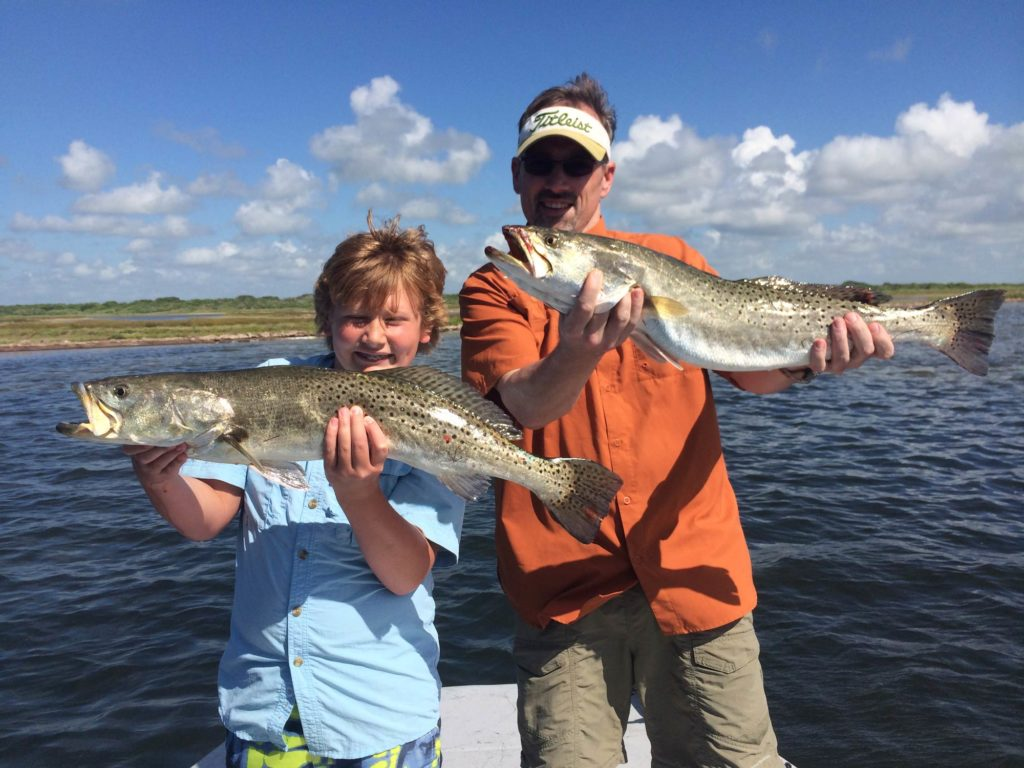 Two young anglers holding big Speckled Trout, with water and blue sky in the background