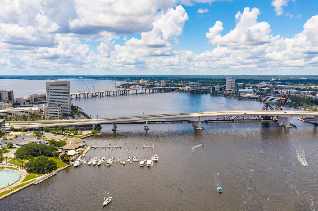 A view of the St Johns River at Jacksonville, with a bridge crossing over it.