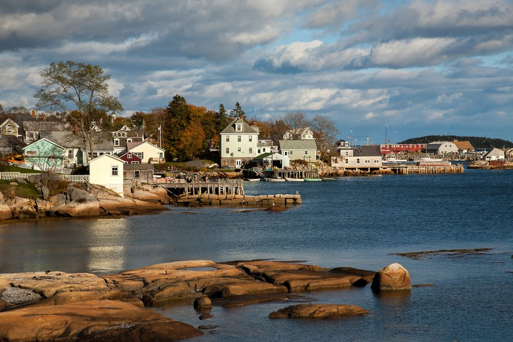 A view from the water of an unspoiled fishing town in Maine, with a small dock and several houses next to the water