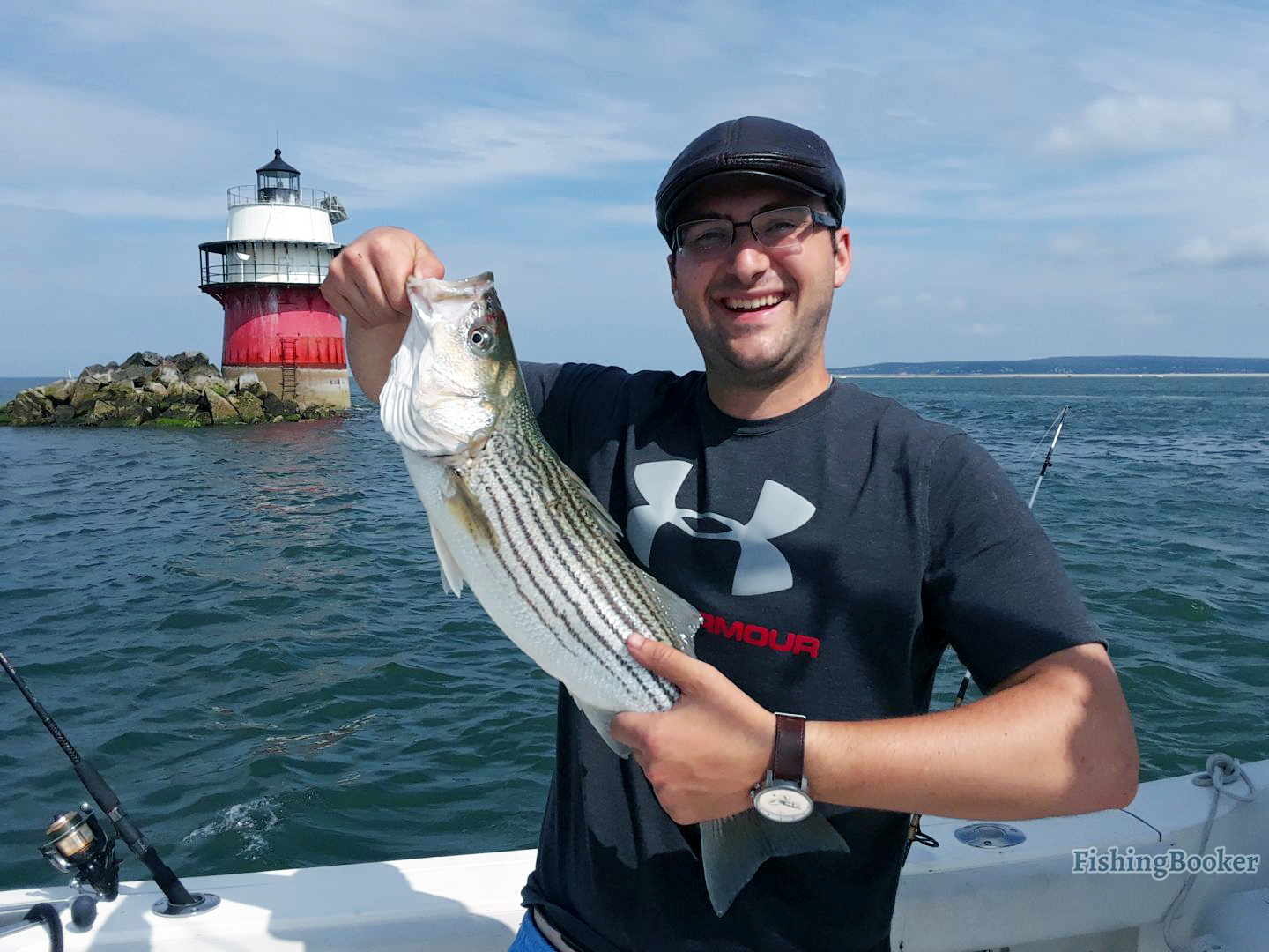 a smiling angler holding a striped bass on a fishing boat near Plymouth, a popular fishing spot near Boston