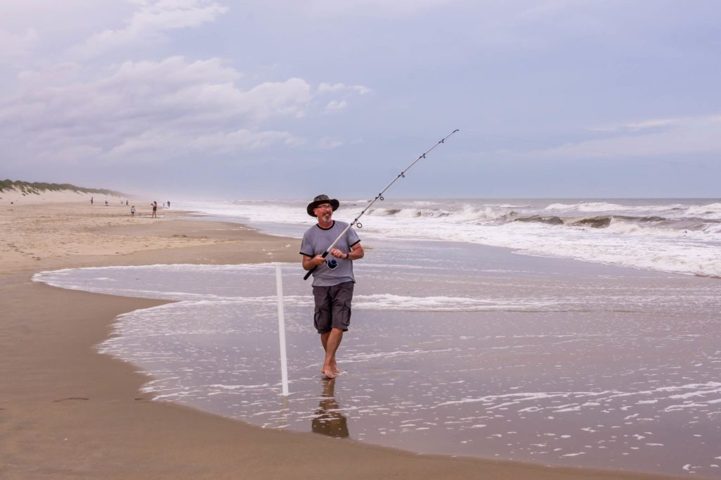 A surf fisherman holding a rod while standing in surf on a North Carolina Beach