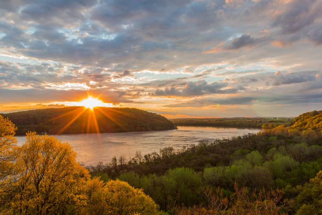 A stunning view of the sunset over Susquehanna River, with surrounding woods and slightly cloudy skies