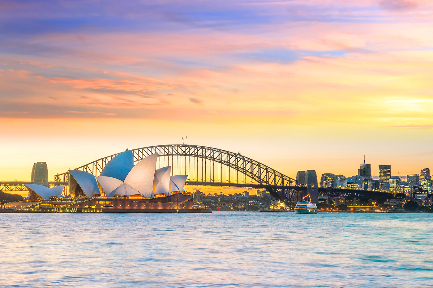 A view of Sydney Harbour from the water at sunrise, with the Harbour Bridge and Sydney Opera House