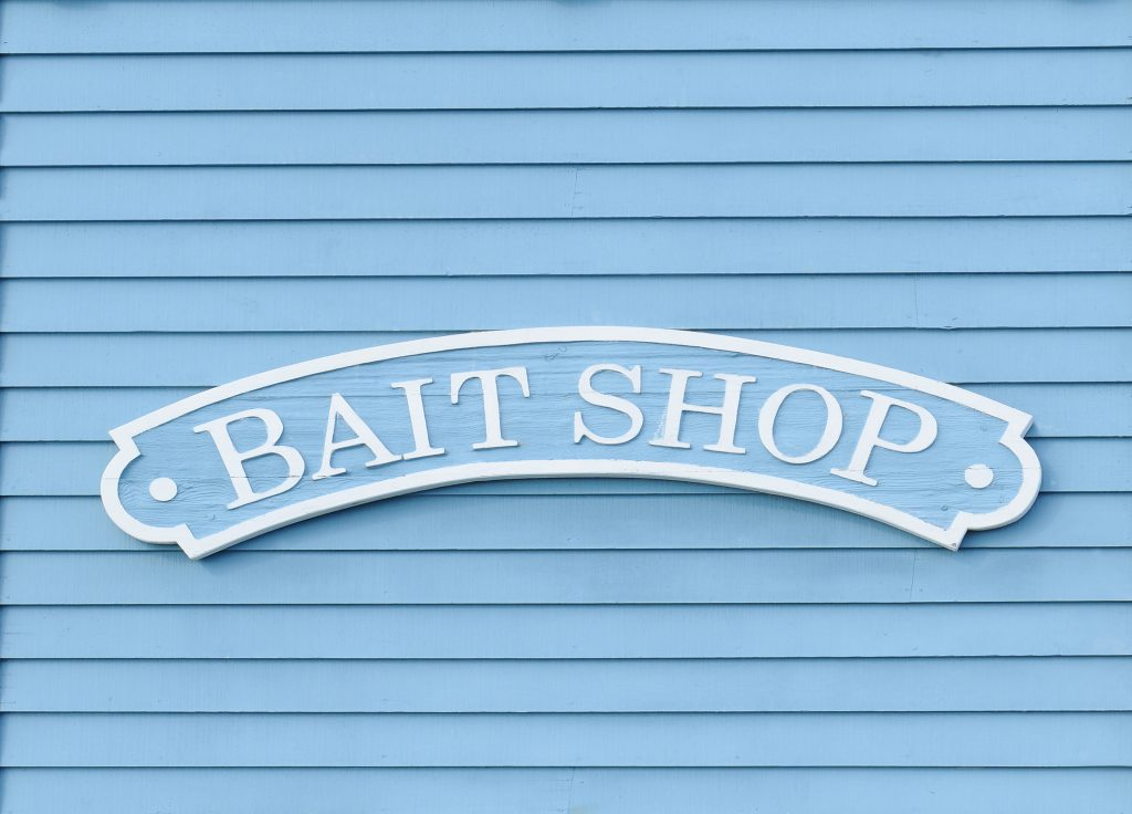 A sign on a wooden wall advertising a bait shop, a common place to buy a fishing license in California