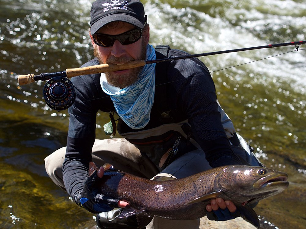 A happy angler with a fly rod holding a a big Taimen Trout