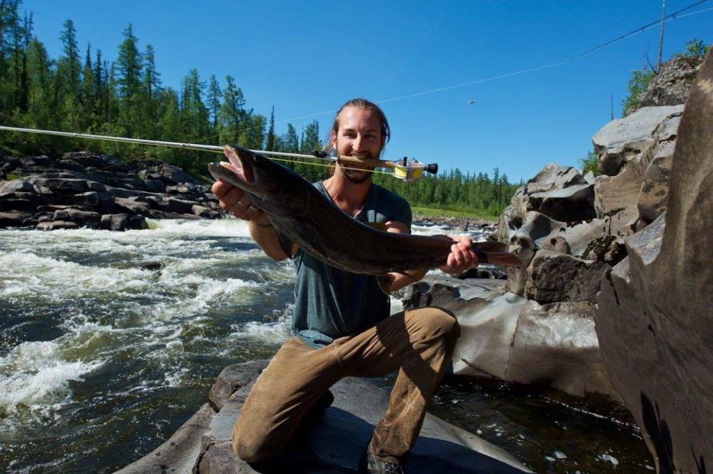 A smiling fisherman holding a huge Taimen Trout with gorgeous nature in the background