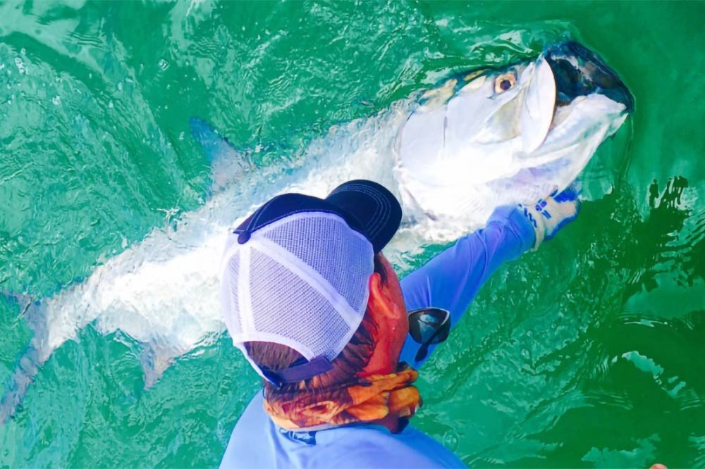 An angler holds a Tarpon near the side of the boat caught while fishing in Destin