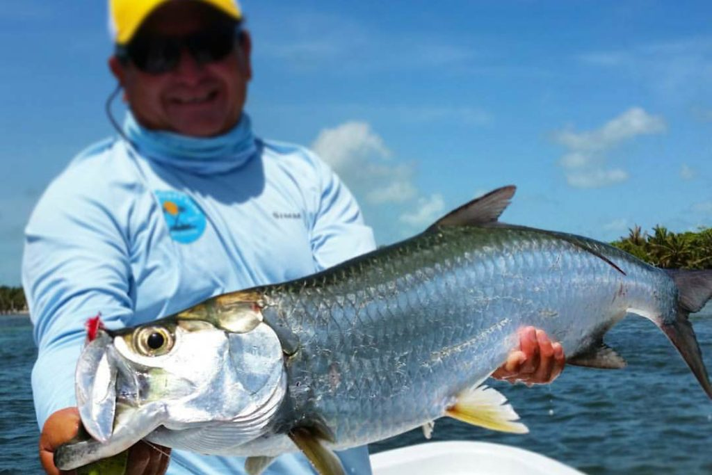 An angler holds a Tarpon caught fishing in Belize
